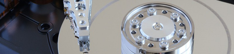 The interior platter of a damaged hard drive with scoring on the surface.